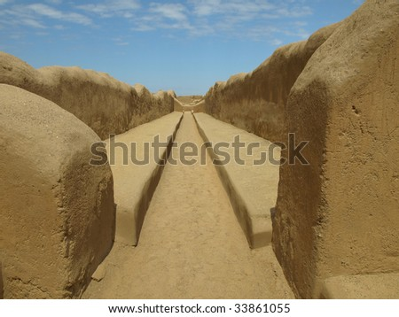 Walls and path inside the ancient adobe city of Chan Chan, remains of the Chimu Empire. Located outside the modern city of Trujillo, northern Peru, South America. - stock photo