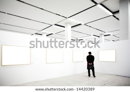 walls in museum with empty frames and person looking - stock photo