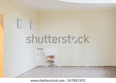 Walls of unfinished renovated living room. The heating system also are partially unfinished. - stock photo