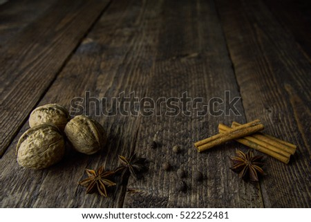 walnut anise cinnamon sticks and pepper on a wooden background