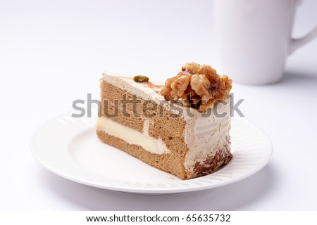 Walnut cake on the white plate with a cup of coffee - stock photo