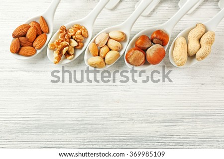 Walnut kernels, almonds, pistachios, hazelnuts and peanuts in the ceramic spoons on the wooden table - stock photo