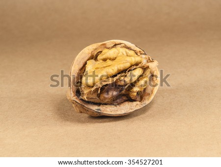Walnut kernels and whole walnuts on kraft paper, close up - stock photo