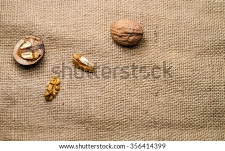 Walnut kernels and whole walnuts on rustic old wooden table,horizontal photo - stock photo