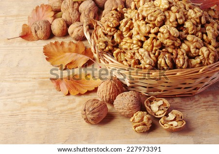 Walnut kernels in basket and whole walnuts on rustic old wood - stock photo