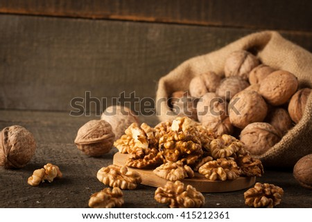 Walnut kernels in sack and whole walnuts on rustic old wood. - stock photo