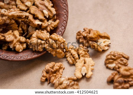 walnut kernels spilled from brown pottery bowl on paper - stock photo