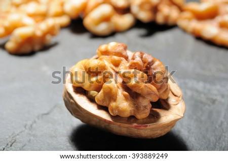 Walnut whole, half shelled close up with shelled walnuts on black slate background. Selective focus. - stock photo