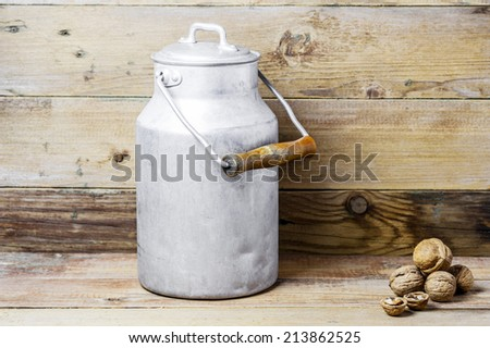 Walnuts and an aluminum old milk can on a wooden background - stock photo