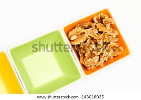 Walnuts and colorful snack serving bowls on white background.