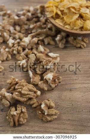 Walnuts and cornflakes on wooden spoon - stock photo