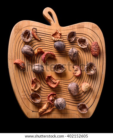 Walnuts and dried fruits on a wooden board in apple form on black background, top view - stock photo