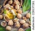 Walnuts, bottle of nut oil and basket on old kitchen table. Top view. - stock photo