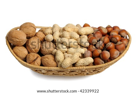 Walnuts, hazelnuts and peanuts in a wicker basket on a white background, isolated