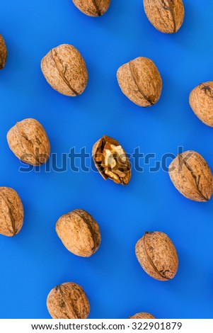 Walnuts in a unique pattern on blue background - stock photo