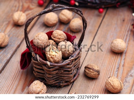 Walnuts in a vintage basket with Christmas background. Russian tradition to eat nuts on Christmas holidays. Selective focus - stock photo