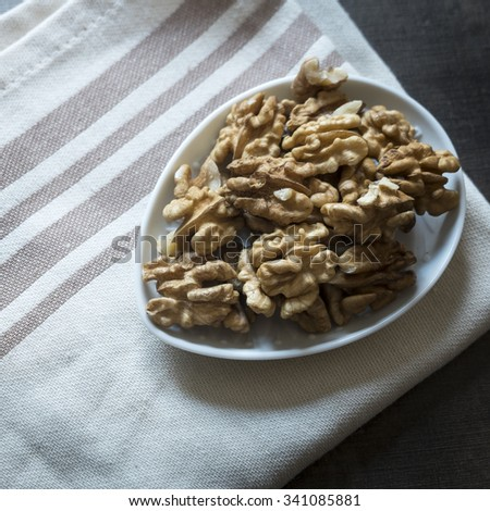 Walnuts in bowl on wooden table. From above - stock photo