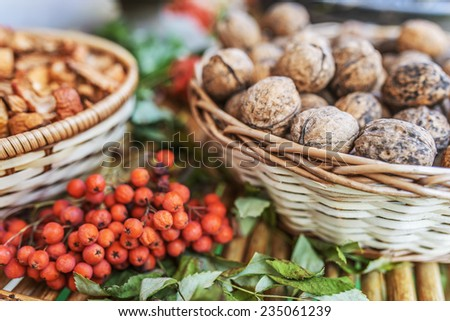Walnuts in wicker basket on background of mountain ash berries and dried fruit. - stock photo