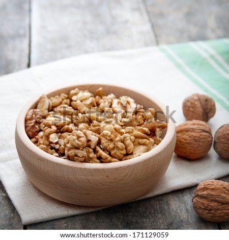 Walnuts in wooden bowl on wooden table - stock photo
