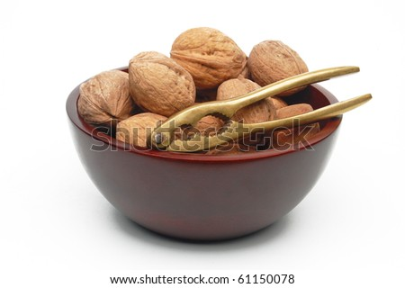 Walnuts in wooden bowl with brass nutcracker - stock photo