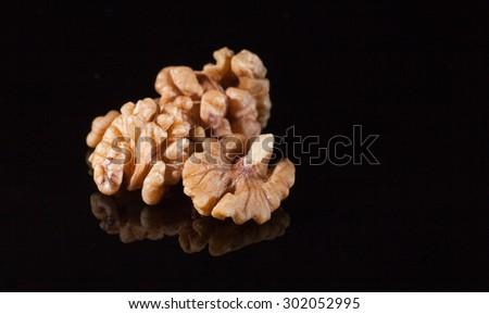 Walnuts isolated on black background. With reflection and copy space - stock photo