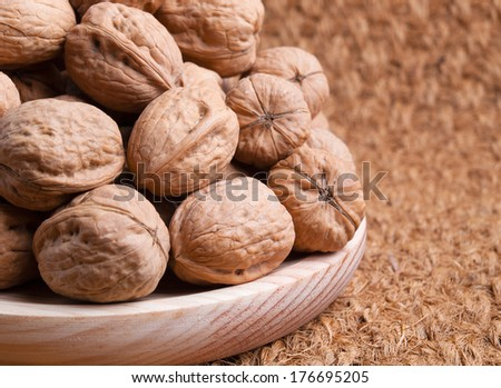 Walnuts on a wooden plate and on a straw background