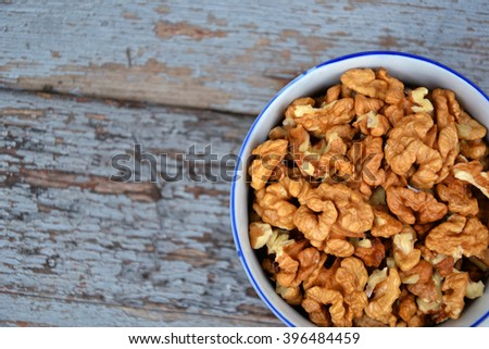 Walnuts. Walnut kernels. Clean organic walnuts. Nuts in the cup on vintage blue wooden background. Countryside agriculture. Walnut tree fresh fall harvest in the village. - stock photo