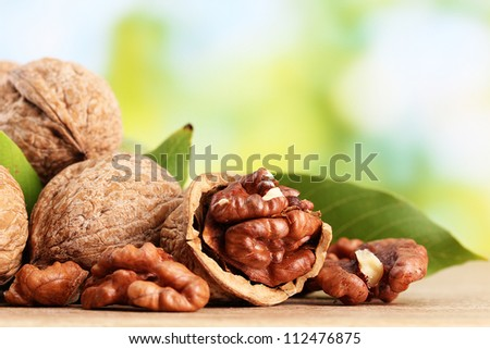 walnuts with green leaves, on green background - stock photo