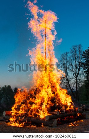 walpurgis night burning wood and religion cross with huge flames - stock photo