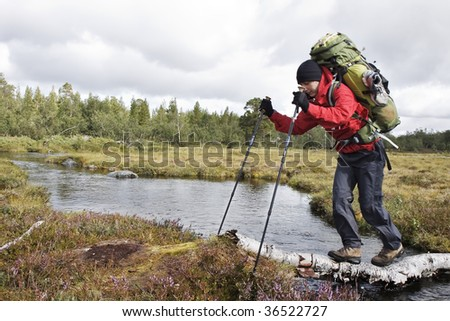 wanderer balanced over the river - stock photo