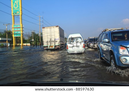 WANG NOI, THAILAND - NOVEMBER 11: Cars navigate through the flood on Phahonyothin Road during the worst flooding in Wang noi, Thailand on November 11, 2011.