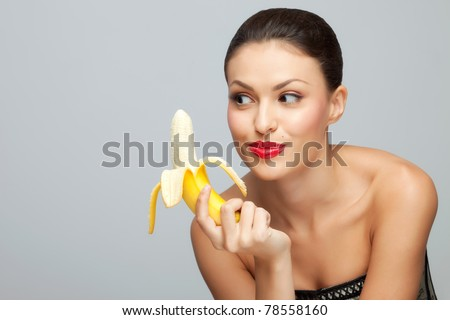 Wanna some? A starving sexy woman holding a half-peeled banana in her hand. - stock photo