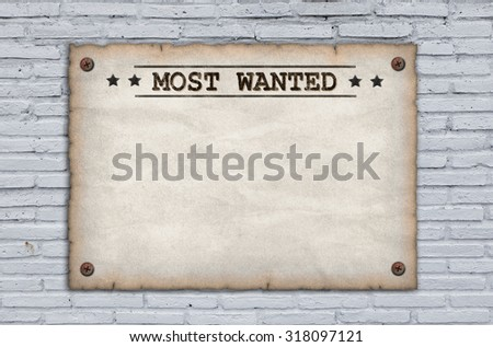 Wanted dead or alive grungy faded posters on brick wall - stock photo