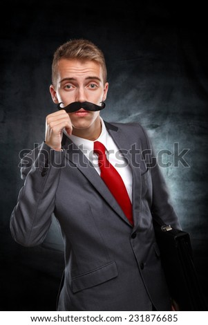 Wants to grow up as soon as possible.Young businessman with fake mustaches pretends to be older isolated on white background - stock photo