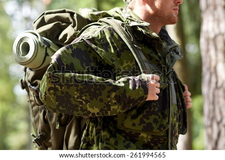 war, hiking, army and people concept - close up of young soldier, ranger or hunter with backpack walking in forest