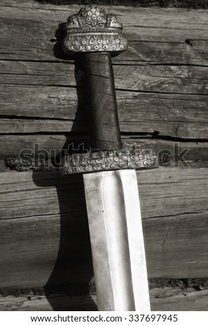 War symbol. Medieval viking sword against a wooden wall - stock photo