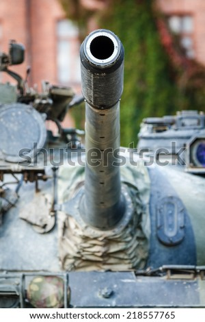 War tank turret closeup. A barrel of a military tank pointed to the sky. Old barrack building on the background. - stock photo