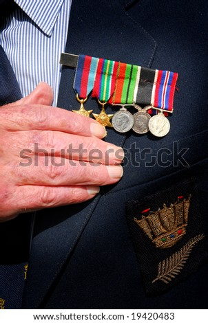 War veteran with hand over heart and war medals - stock photo