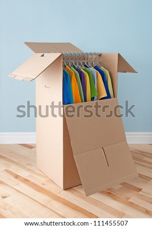 Wardrobe box filled with colorful clothing, prepared for transportation.