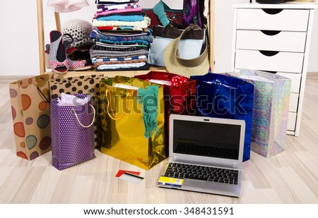 Wardrobe with clothes and shopping bags, on line shopping. Close up on a laptop and credit cards, internet buying for Christmas, many full bags in a woman closet. - stock photo