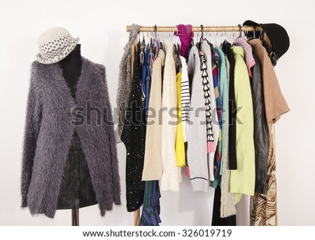Wardrobe with clothes arranged on hangers and a winter outfit on a mannequin. Dressing closet with autumn clothes and accessories. Tailor's dummy wearing a fluffy grey sweater with scarf and hat. - stock photo