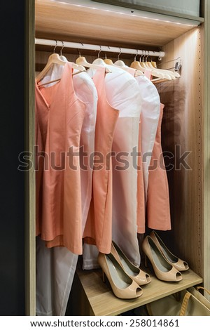 Wardrobe with clothes on hangers - stock photo