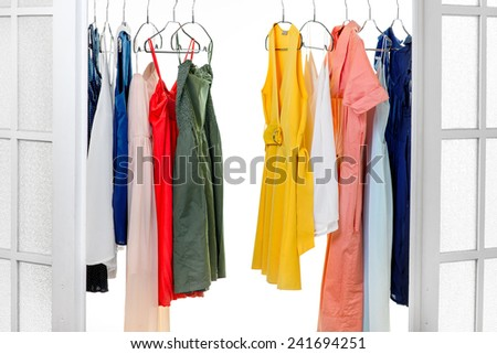 Wardrobe with colorful dresses on hangers on white background