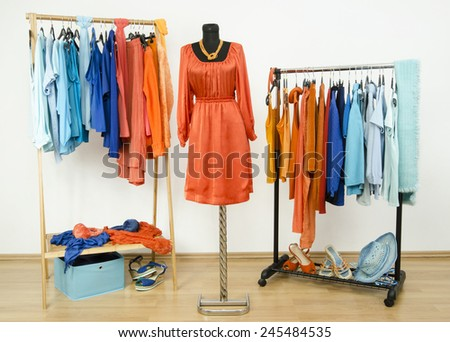 Wardrobe with complementary colors orange and blue clothes arranged on hangers. Dressing closet with clothes, shoes and accessories and a dress on a mannequin. - stock photo