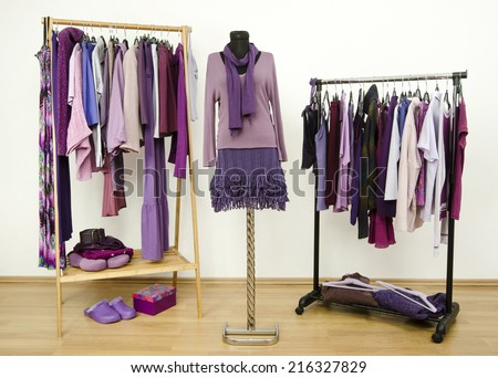 Wardrobe with purple clothes arranged on hangers and an outfit on a mannequin.  Dressing closet with all shades of violet clothes, shoes and accessories. - stock photo