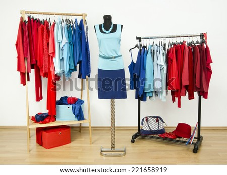 Wardrobe with red and blue clothes arranged on hangers. Dressing closet with clothes, shoes and accessories and an outfit on a mannequin - stock photo