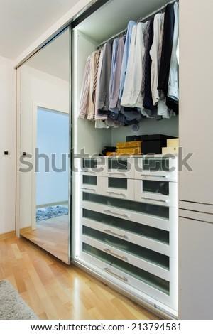 Wardrobe with sliding doors and mirror - stock photo