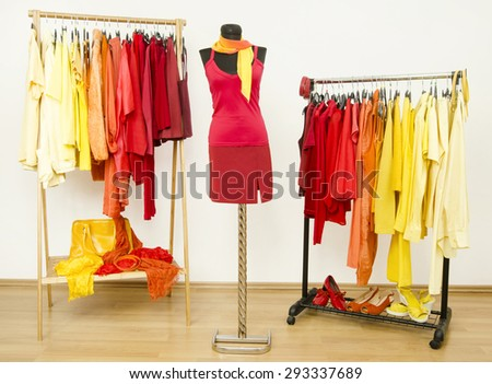 Wardrobe with yellow, orange and red clothes arranged on hangers and a red outfit on a mannequin. Dressing closet with bright color coordinated clothes on hangers, shoes and accessories. - stock photo