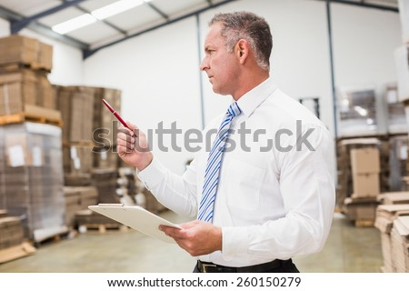 Warehouse boss checking his inventory in a large warehouse - stock photo
