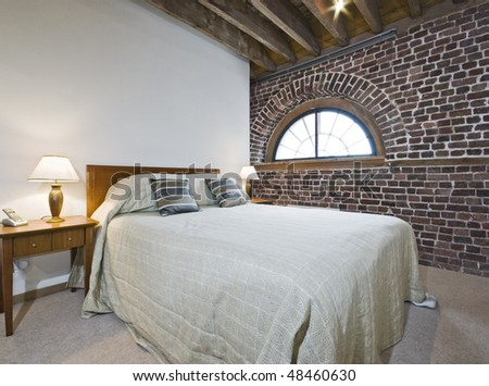 warehouse conversion bedroom with exposed brick work - stock photo